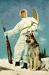 Snow Soldier with German Shepard on top of the mountain.